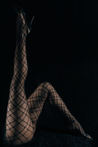 Low key photo of sexy slim beautiful legs in black net tights against black background